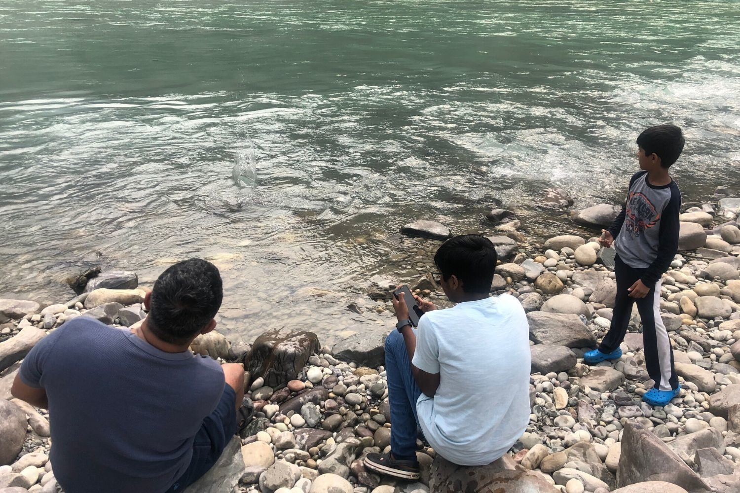 The boys trying their hand at skipping stones at Taj Rishikesh